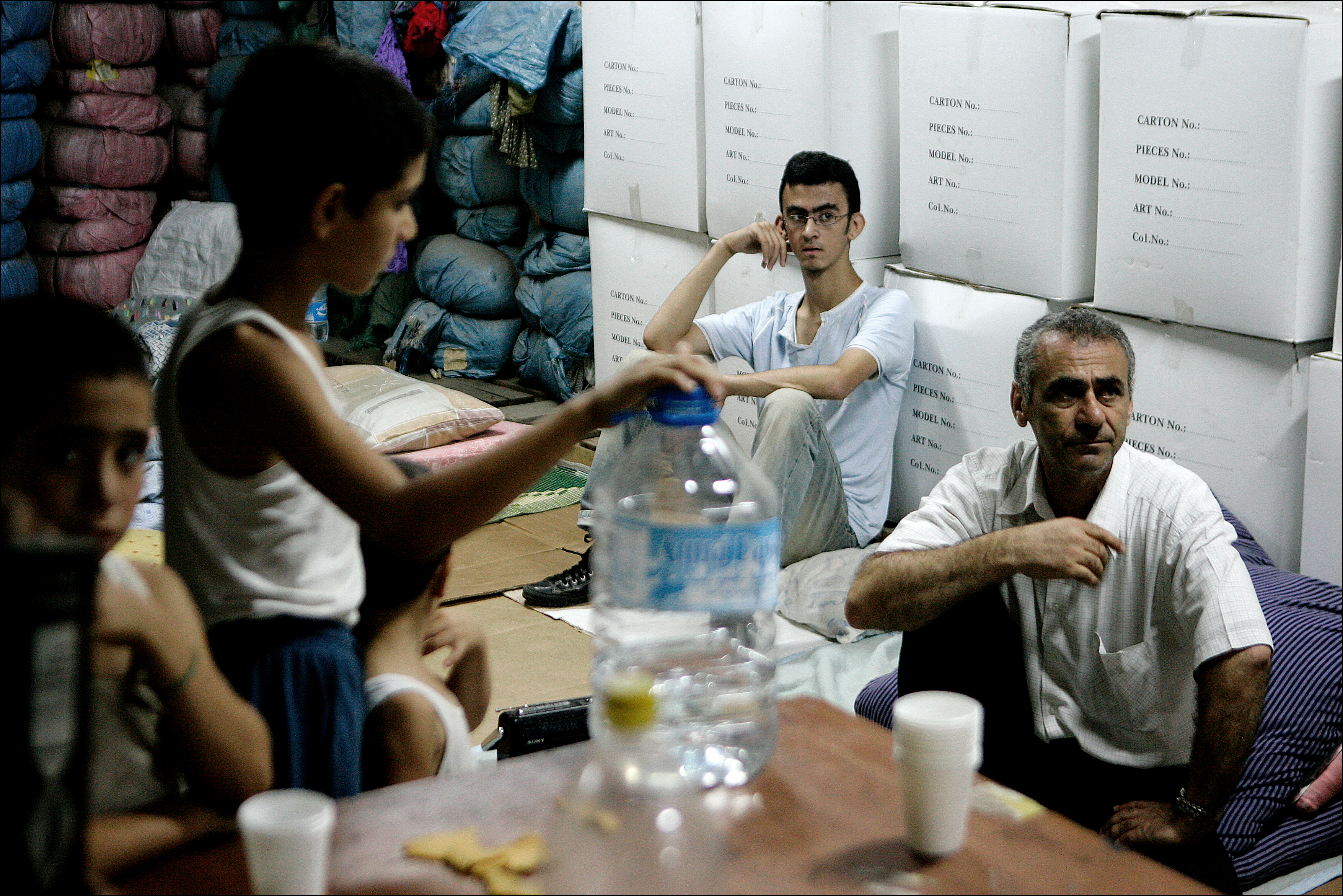 Civilian residents of Dahiyah, the southern Shiite suburb of Beirut, seek refuge in the basement of the targeted Haret Hreik area on July 16, 2006. It is unclear wether they survived the continuing bombardment during the day. Colossal damage was done to the district after Israeli rockets rained down incessantly on Lebanon's capital. Entire apartment buildings dissapeared after Israeli vacuum bombs hit Beirut's Southern Shiite suburb of Dahiyeh incessantly for 3 straight days.