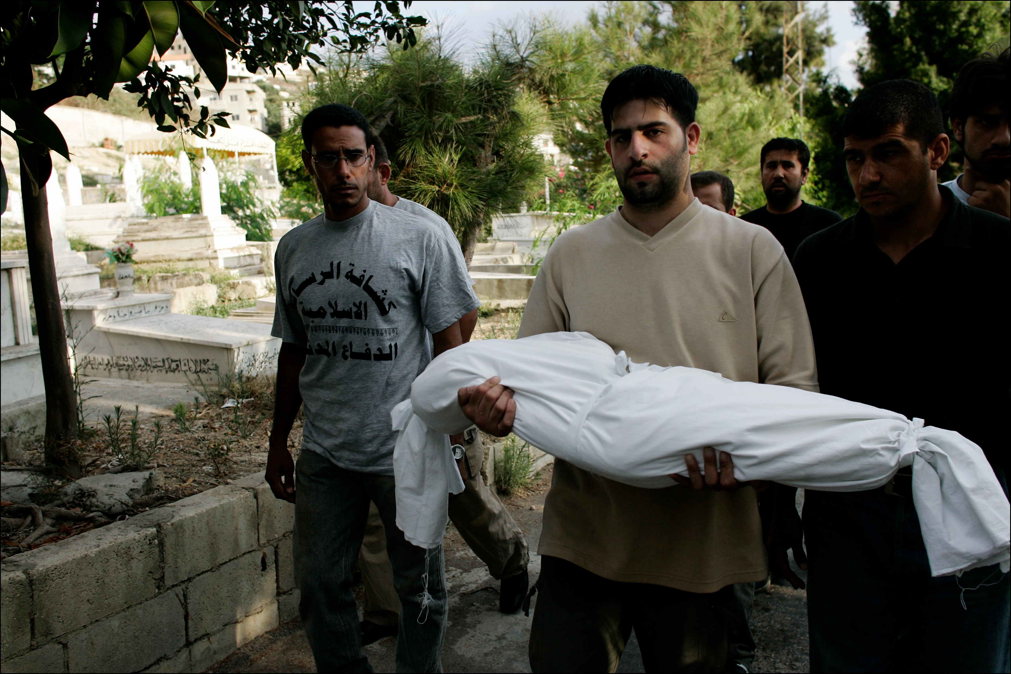 Residents of Ghaziyeh, near Sidon, Lebanon carry the body of 2 year old Malek Jbeiri to a hurriedly made grave. The girl died when an Israeli airstrike targeted her family's building just as a funeral procession for the 15 victims of the previous mornings bombardment passed alongside the building, creating 13 more civilian deaths.