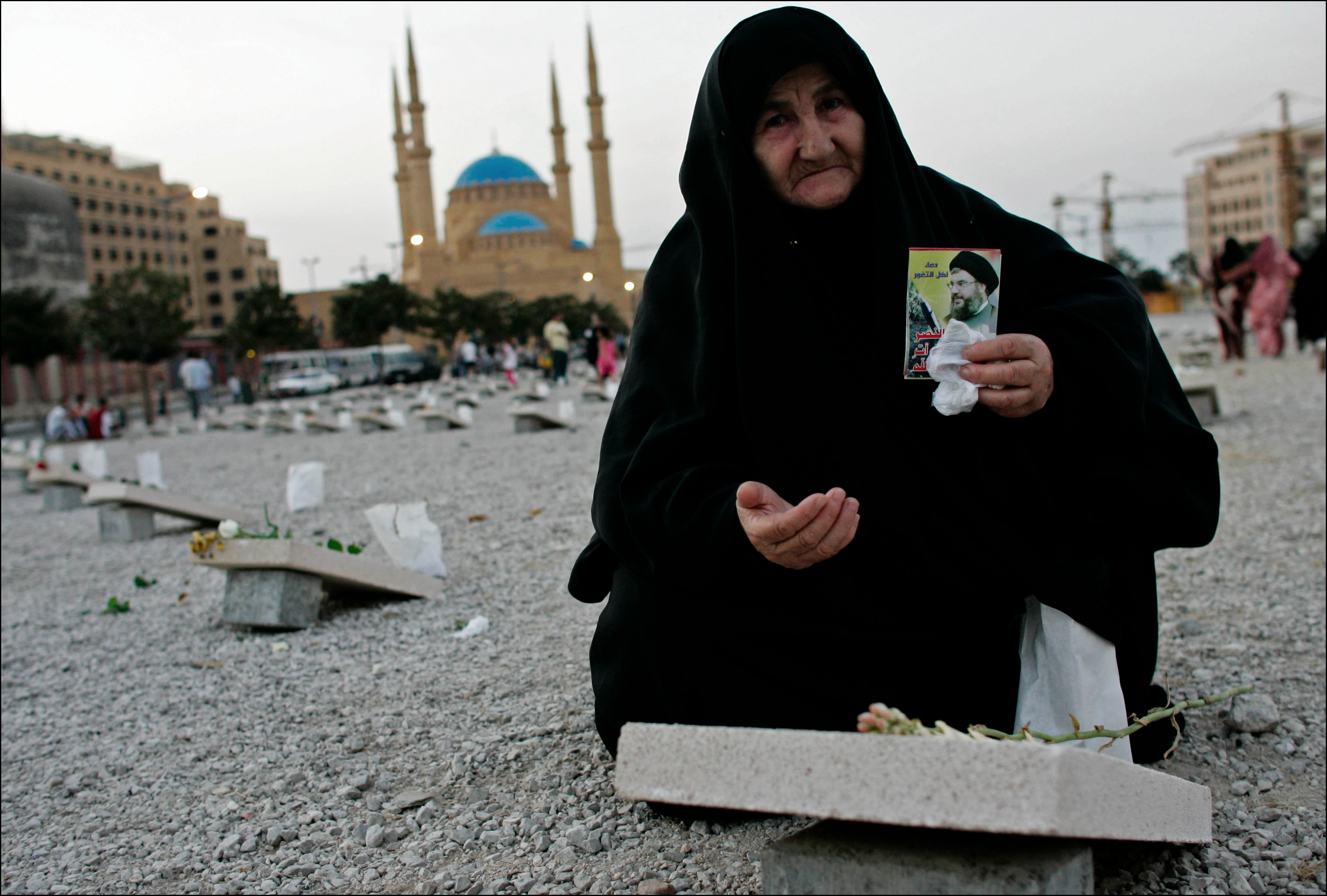 On Beirut's central Martyr's square, a Shiite woman shows a portrait of Hizbollah leader Sayed Hassan Nasrallah over a symbolic tombstone for the Lebanese victims of the Israeli offensive.