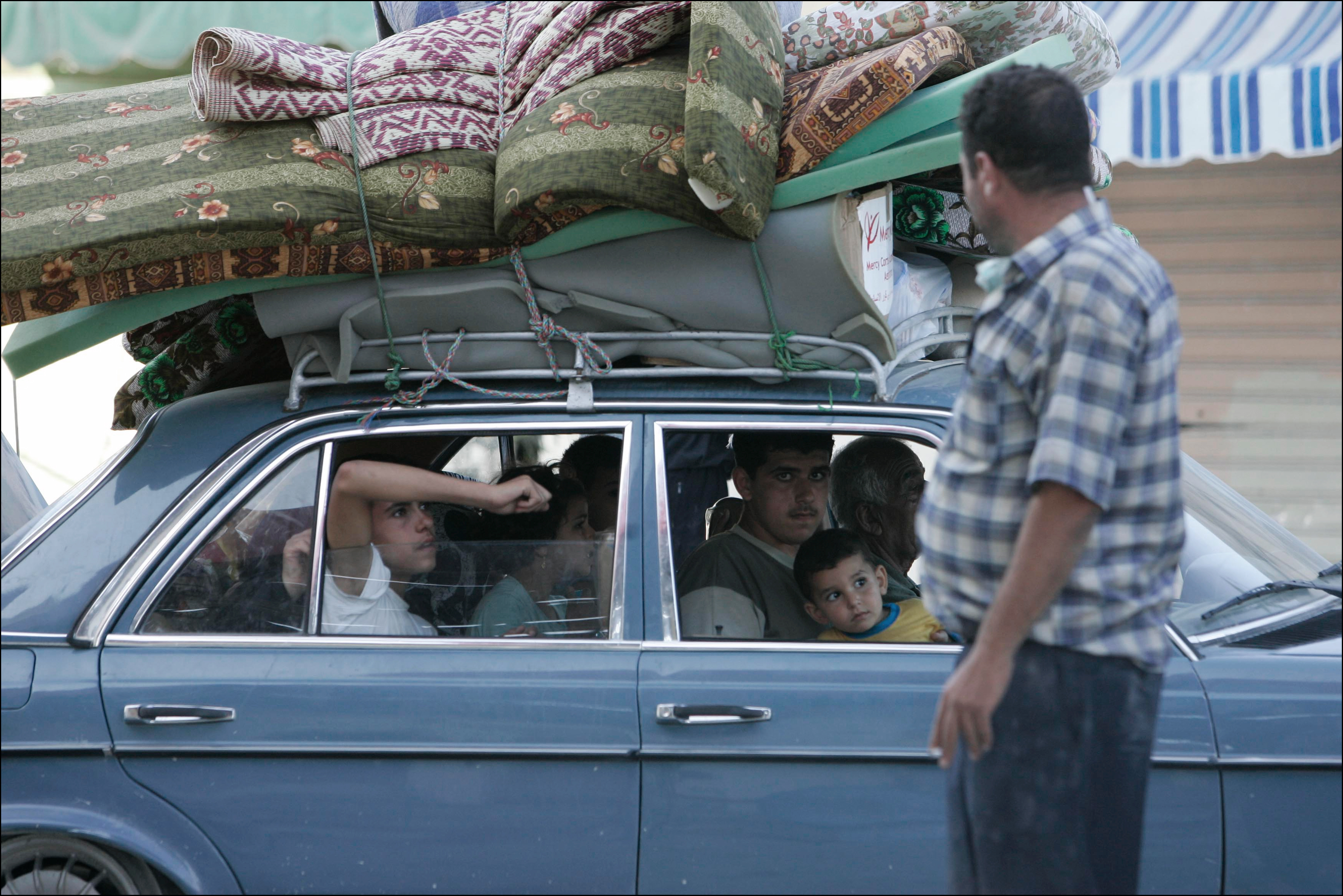 Lebanese refugees drive back to their home towns in southern Lebanon after a ceasefire agreement stopped the fighting. Many Lebanese celebrated what they perceived as the win of Hizbollah after a month long war with Israel. The war lead to over 1000 civilian deaths in Lebanon and vast destruction of the country's infrastructure from heavy Israeli bombardments.