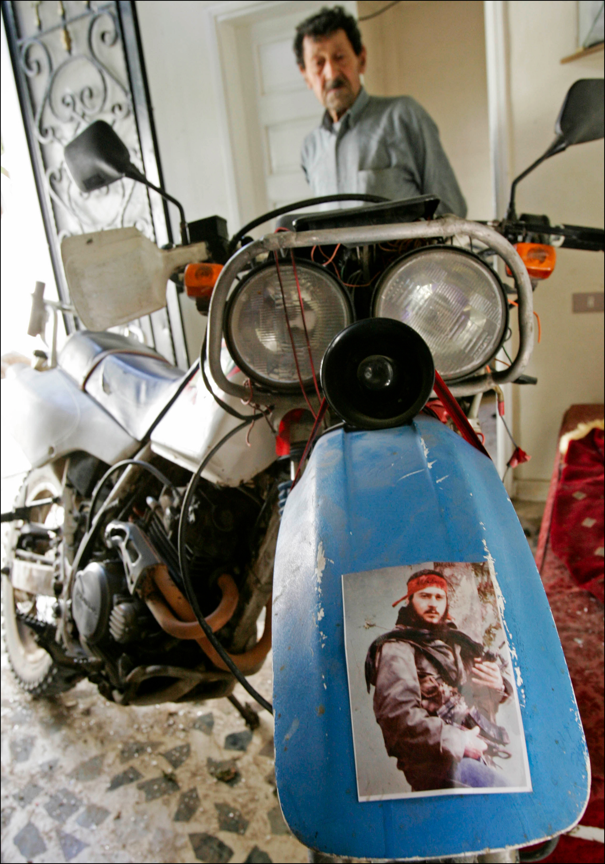 "A relative looks at the motorbike of a Hizbollah fighter standing in the entrance of his home in Aitaroun, 5 kilometers from the border with Israel, a day after a ceasefire agreement between Israel and Lebanon put a temporary end to fighting in the town. The picture glued to his bike shows his cousin, a Hizbollah ""martyr"" who died during an operation against Israeli forces in 1986. Many Lebanese celebrated what they perceived as the win of Hizbollah after a month long war with Israel that lead to over 1500 civilian deaths in Lebanon and vast destruction of the country's infrastructure from heavy Israeli bombardments."