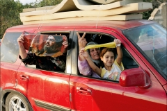 Lebanese refugees show a Hizbollah flag and a portrait of HIzbollah leader Hassan Nasrallah as they drive back to their home towns in southern Lebanon after a ceasefire agreement stopped the fighting. Many Lebanese celebrated what they perceived as the win of Hizbollah after a month long war with Israel that lead to over 1000 civilian deaths in Lebanon and vast destruction of the country's infrastructure from heavy Israeli bombardments.